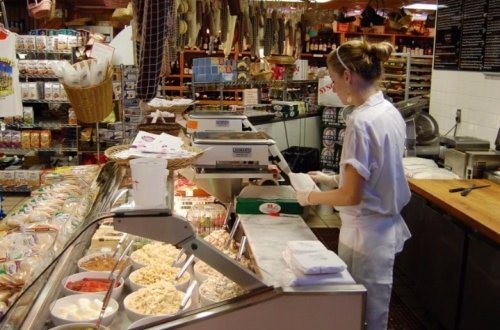 man standing behind deli counter